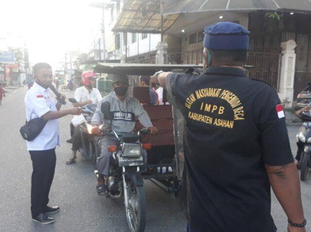 Ketua IMPB Asahan M. Nasir saat memberikan takjil kepada pengemudi becak yang melintas.